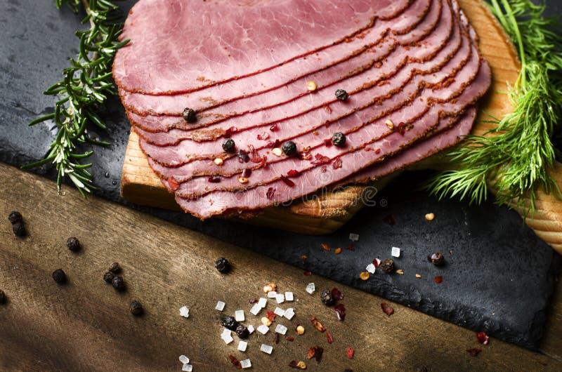 Pastrami affettati freschi del manzo circondati dalle erbe nel choppin di legno fotografie stock