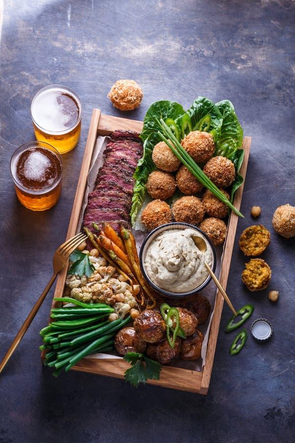 Pastrami, falafel, babagahanoush, vegetarianos e cerveja em uma caixa de madeira, copyspace fotos de stock royalty free