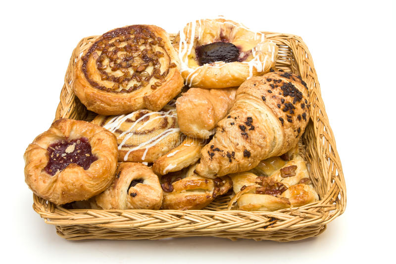 Pastry basket. Wicker basket with selection of French & Danish pastries on white background royalty free stock image