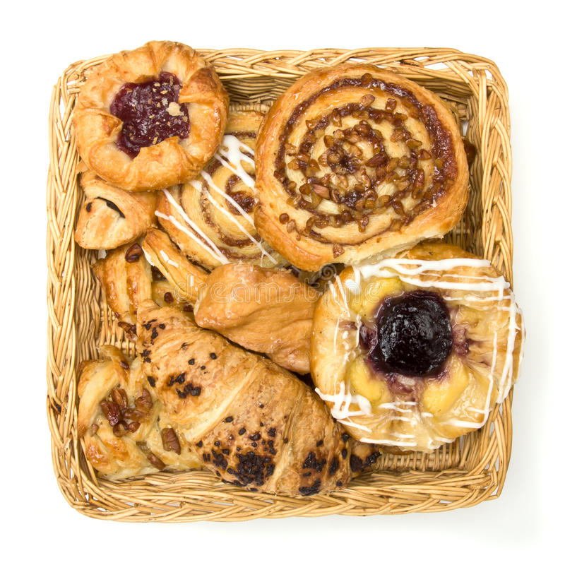 Pastry basket. Overhaead view of Wicker basket with selection of French & Danish pastries on white background royalty free stock images