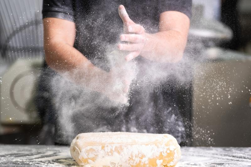 Pastry Chef clapping his hands with flour while making dough stock images