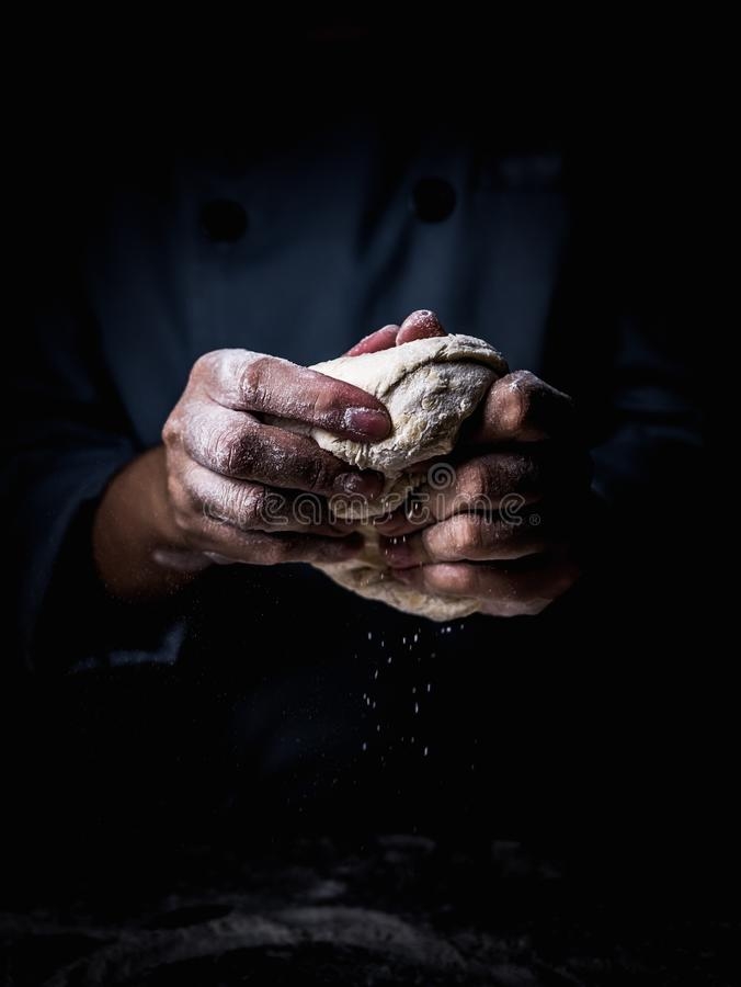 Pastry chef hand kneading Raw Dough with sprinkling white flour.  stock photo