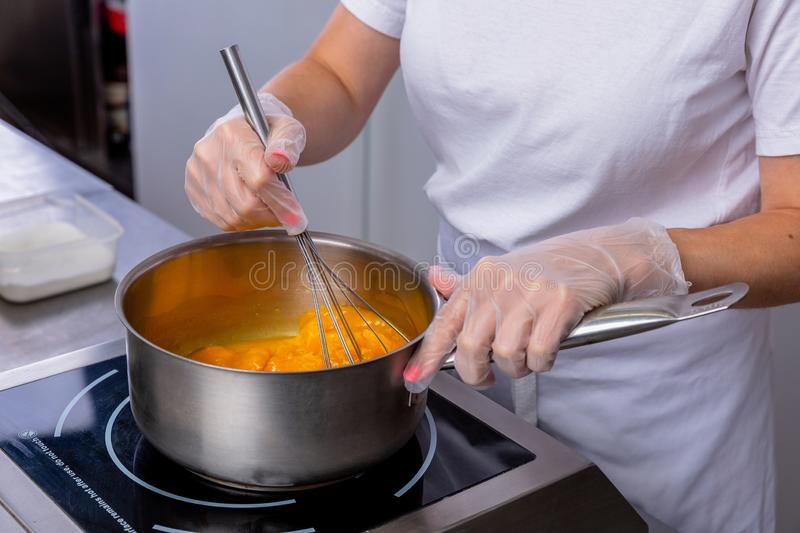 Pastry chef in the kitchen makes passion fruit confit. Chef stirs with a whisk fruit in a pan. Master class in the kitchen. The royalty free stock photo