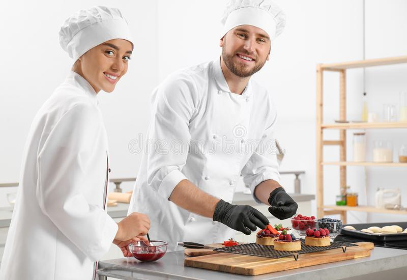 Pastry chefs preparing desserts at table stock photo