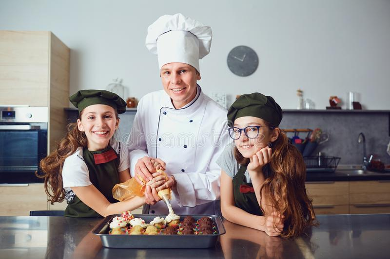 Pastry-cook with girls children prepare cookies in the kitchen. royalty free stock photos