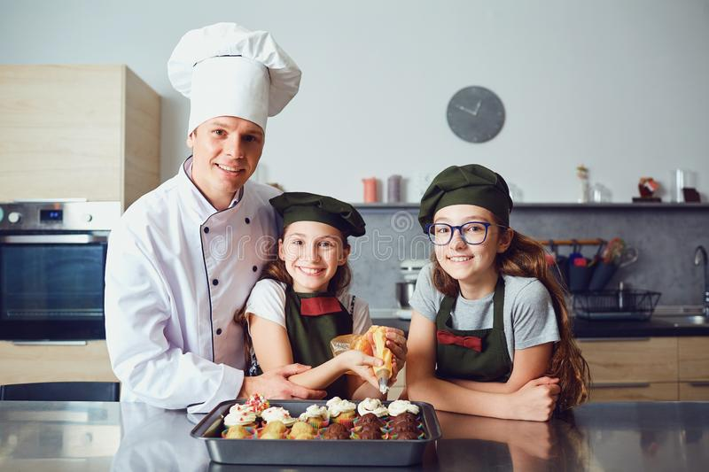 Pastry-cook with girls children prepare cookies in the kitchen. royalty free stock photo