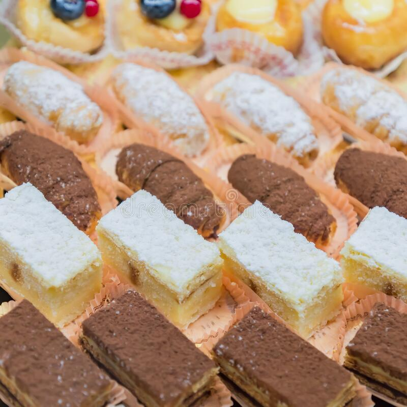 Pastry shop display window with variety of mini desserts and cakes, selective focus.  royalty free stock photo