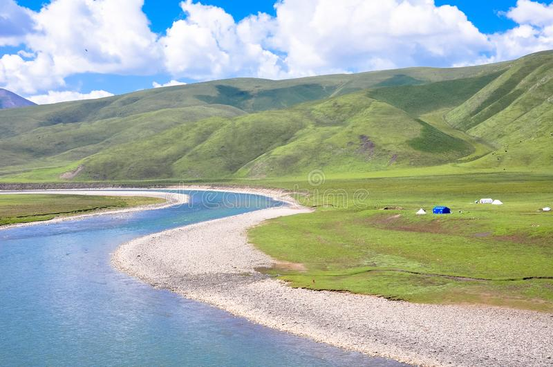 River and prairie on mountain with sheep herd and house royalty free stock image