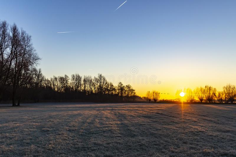 The pasture next to lake Zoetermeerse plas is frosted when the sun rises and the sky gets wonderful colors.  royalty free stock image