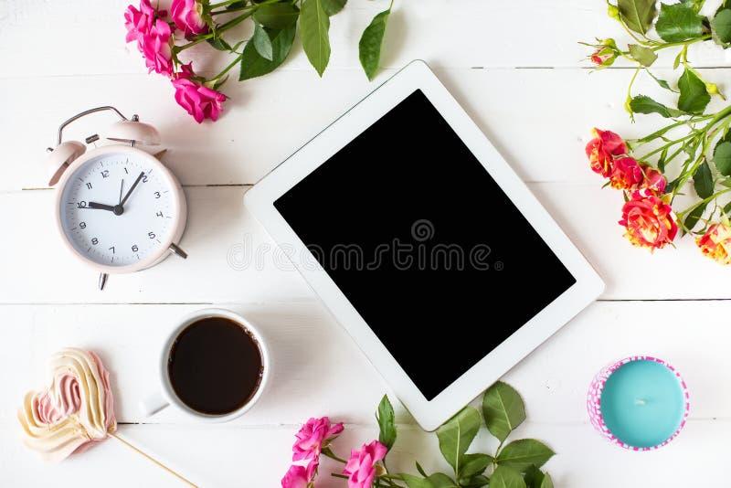 Pastylka, budzik, filiżanka kawy, róże, świeczki na stole Kobiet rzeczy mody kobiet biurko fotografia stock