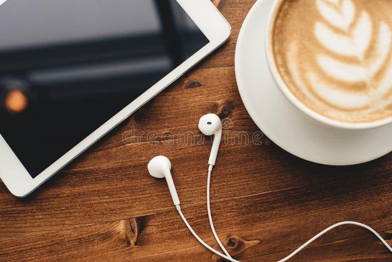 Pastylka, hełmofony i cappuccino z latte sztuką, zdjęcie royalty free