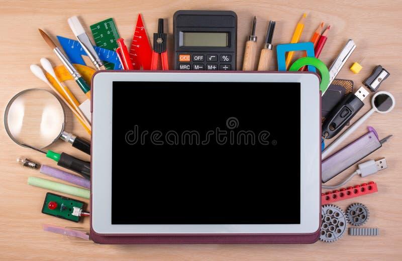 Pastylka pecet nad szkolnymi dostawami lub biurowymi dostawami na szkoła stole fotografia stock