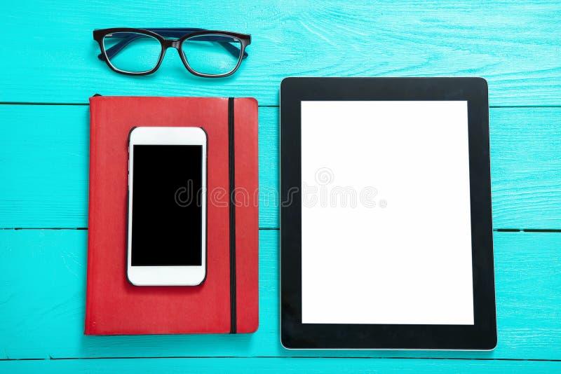 Pastylka z pustym ekranem i smartphone z kopii przestrzenią na akcesoriach na błękitnym drewnianym tle ekranu i edukaci zdjęcie royalty free