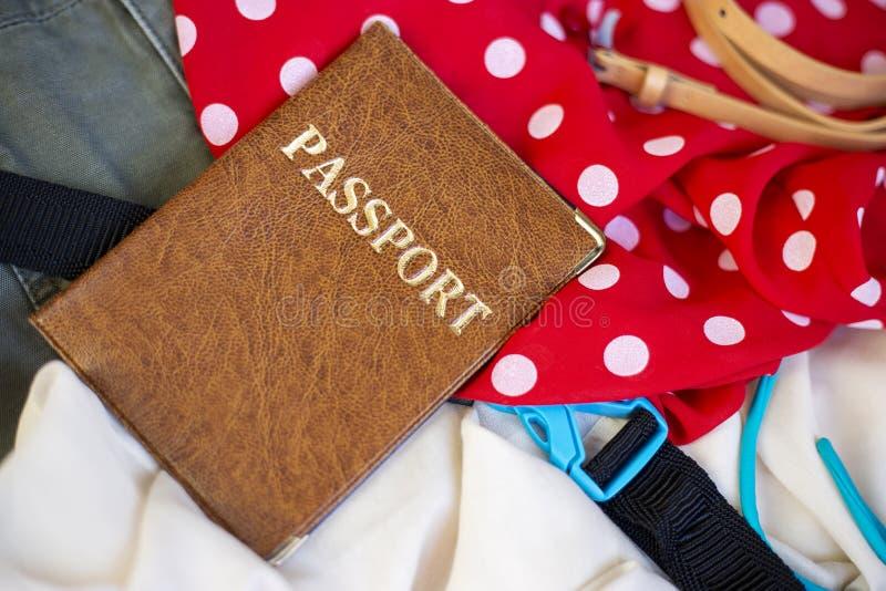 Paszport i odziewa w rozpieczętowanej walizce fotografia stock