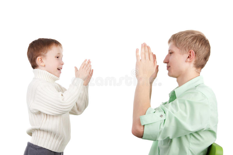 Pat-a-cake. Cute little boy playing pat-a-cake with his elder brother stock images