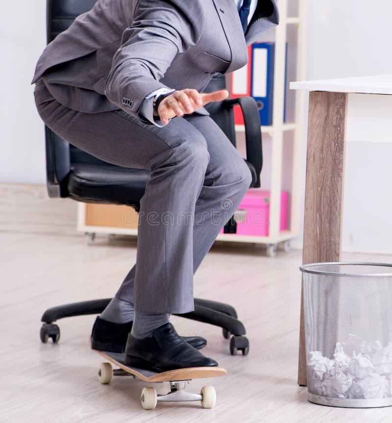 Pat?n joven del montar a caballo del hombre de negocios en oficina durante rotura fotos de archivo libres de regalías