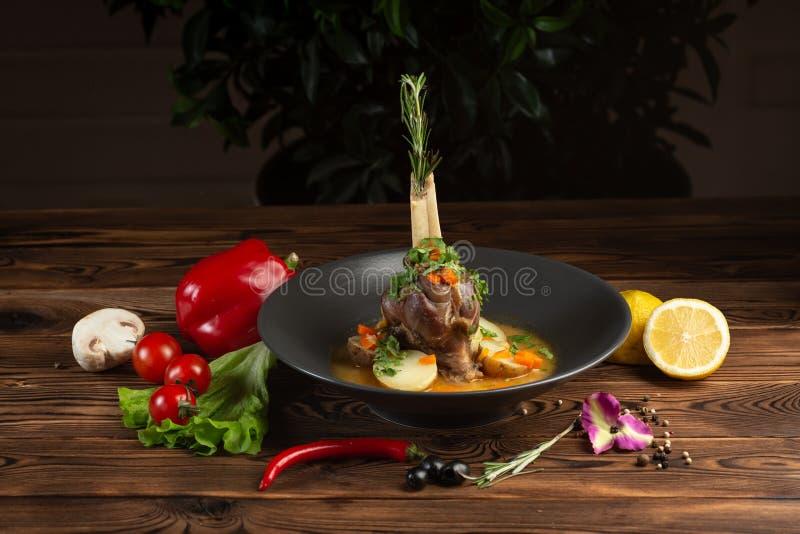 Pata cozida do cordeiro com ervas orientais e vegetais fotos de stock