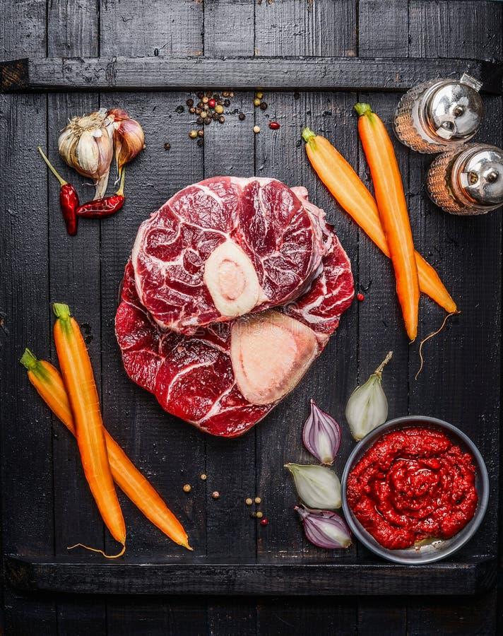 A pata crua da vitela corta a carne e os ingredientes para Osso Buco que cozinha no fundo de madeira preto imagem de stock