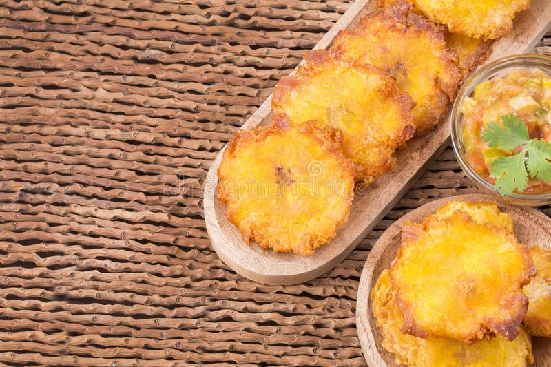 Patacon or toston fried and flattened pieces of green plantain, traditional snack or accompaniment in the Caribbean, guacamole and. Tomato onion salad beside royalty free stock image