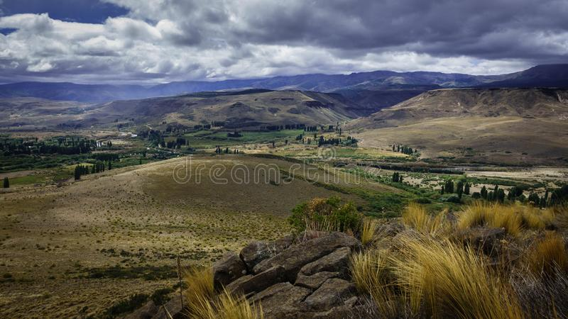 Patagonian landscape of huge hills covered with shrubs, rocks, some trees and a sky full of clouds. stock photography