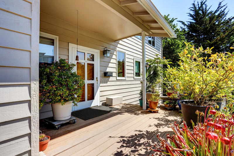 Patamar de madeira agradável do assoalho com flores e arbustos ao redor Porta de entrada branca dianteira imagem de stock royalty free