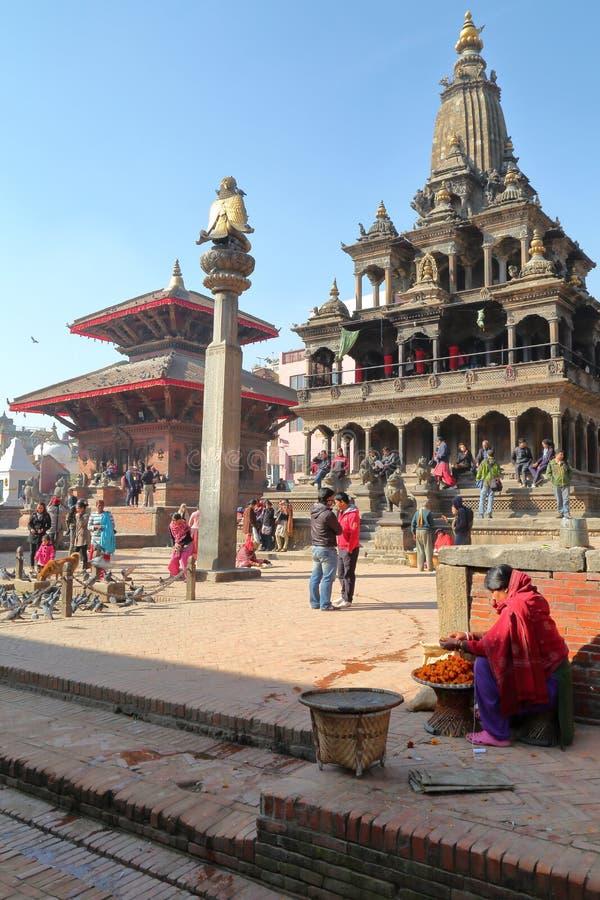 PATAN, NÉPAL - 19 DÉCEMBRE 2014 : La statue de Garuda sur la colonne et le temple de Krishna Mandir chez Durbar ajustent photos stock