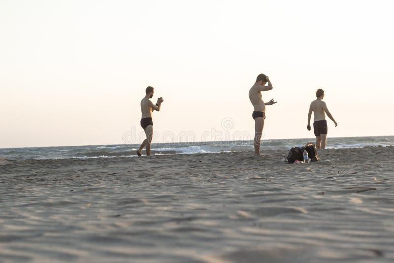 PATARA - FETHIYE, TURQUIA - 22 DE AGOSTO DE 2018 Tiro limpo do standıng dos homens na praia no tempo do por do sol fotos de stock