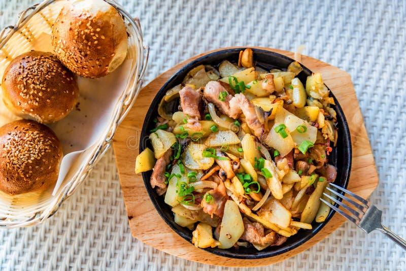 Patata arrostita in padella con carne ed il porro verde fotografia stock libera da diritti