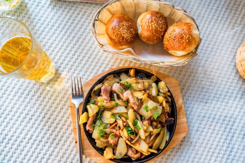 Patata arrostita in padella con carne ed il porro verde fotografia stock