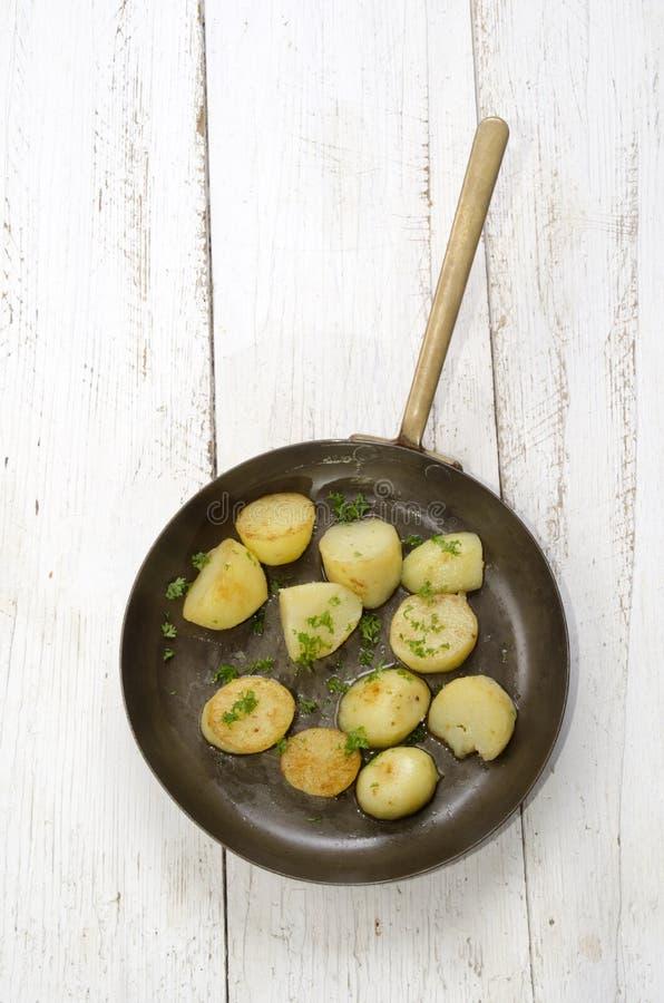 Patata asada con perejil en una cacerola de cobre foto de archivo