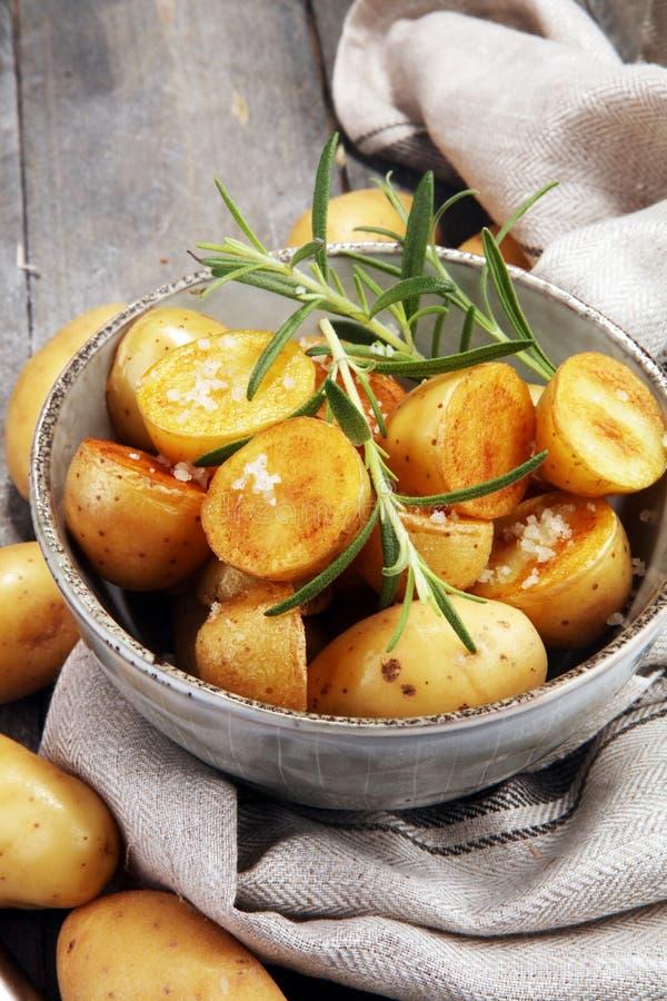 Patata asada con romero fresco en un cuenco fotos de archivo