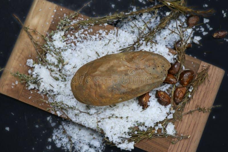 Patata cocida en la sal de roca foto de archivo