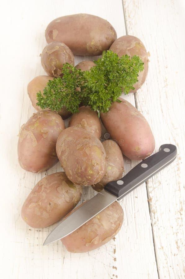 Patata cruda con perejil y el cuchillo fotos de archivo libres de regalías