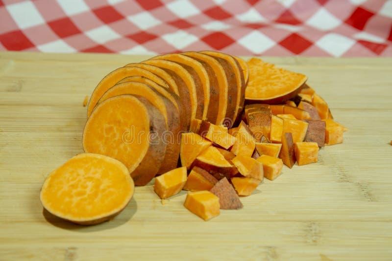 Patata dolce affettata e tagliata su un tagliere fotografia stock