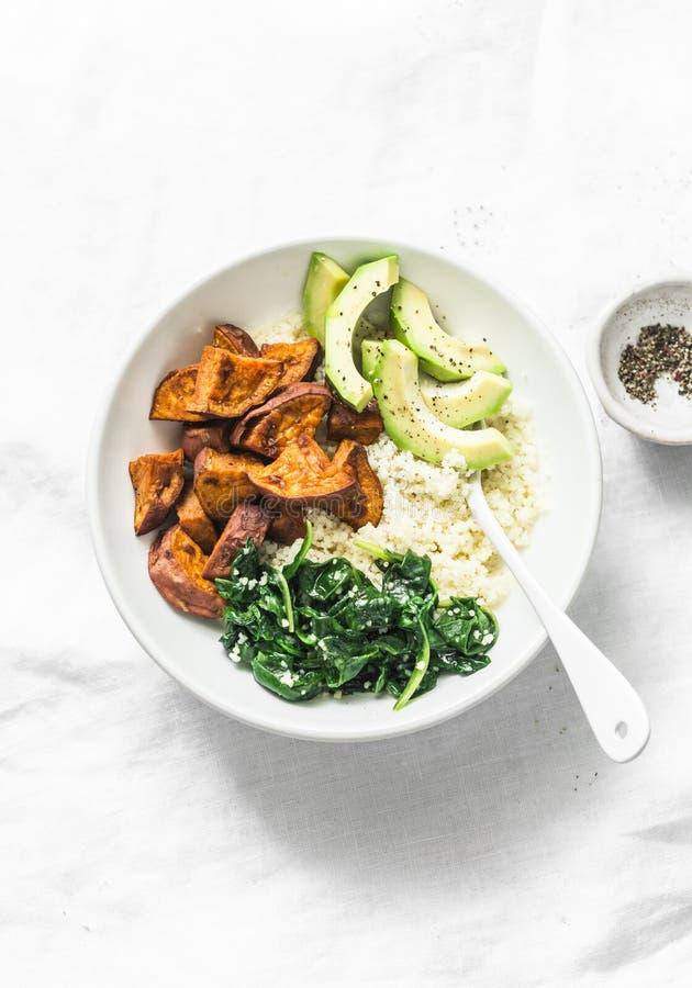 Patata dolce, cuscus, spinaci, ciotola di Buddha dell'avocado su fondo leggero, vista superiore Alimento vegetariano di comodità immagine stock