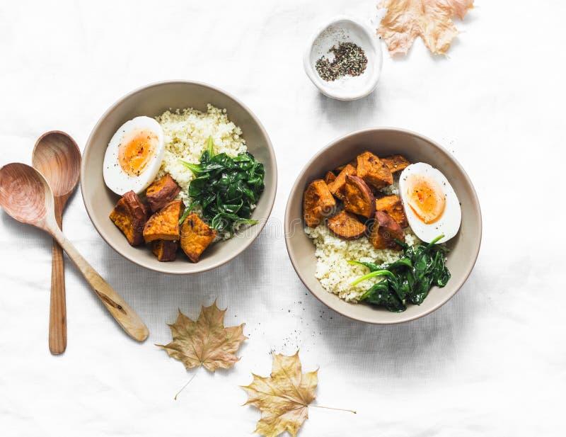Patata dolce, cuscus, spinaci, ciotola di Buddha dell'uovo su fondo leggero, vista superiore Alimento vegetariano fotografia stock