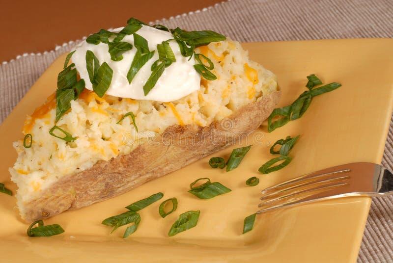Patata due volte cotta con gli scallions, il formaggio e la crema acida fotografia stock