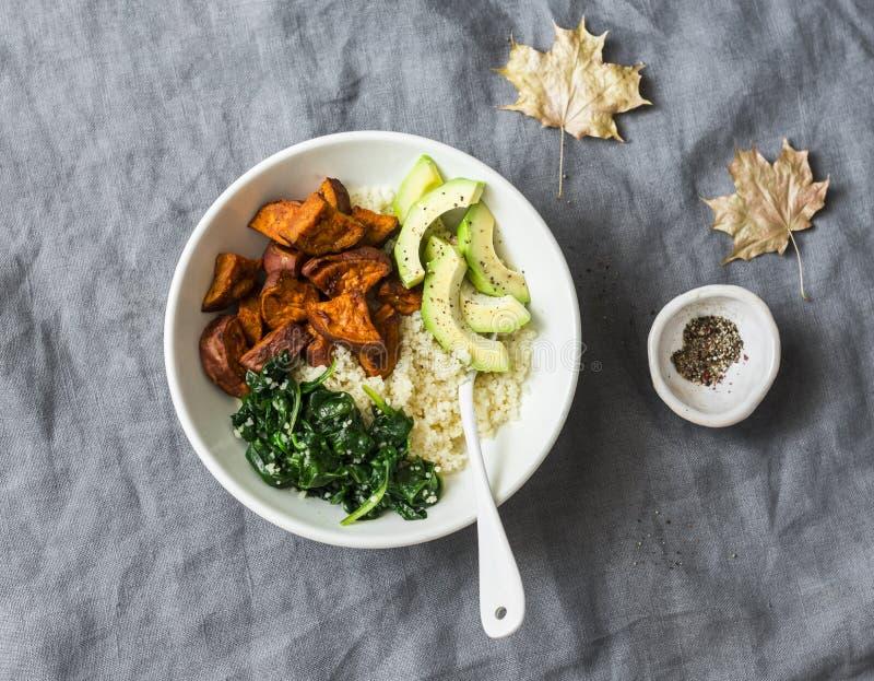 Patata dulce, cuscús, espinaca, cuenco de Buda del aguacate en el fondo gris, visión superior Comida vegetariana de la comodidad foto de archivo