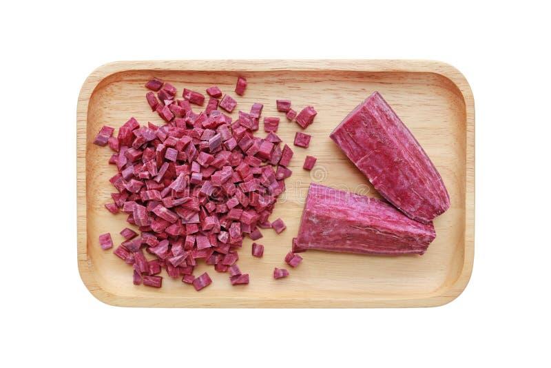 Patata dulce púrpura tajada y cortada en la bandeja de madera aislada en el fondo blanco imagen de archivo