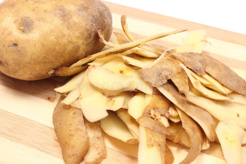 Patata entera y cáscaras que mienten en tabla de cortar de madera fotos de archivo