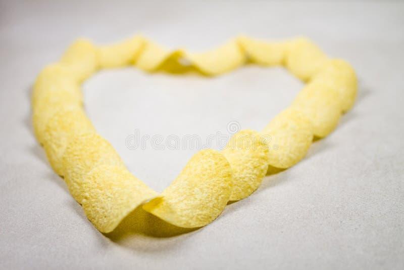 Patata gialla multipla Chips Heart Formation Composition Isolated sopra Gray Grey White Background leggero fotografia stock libera da diritti