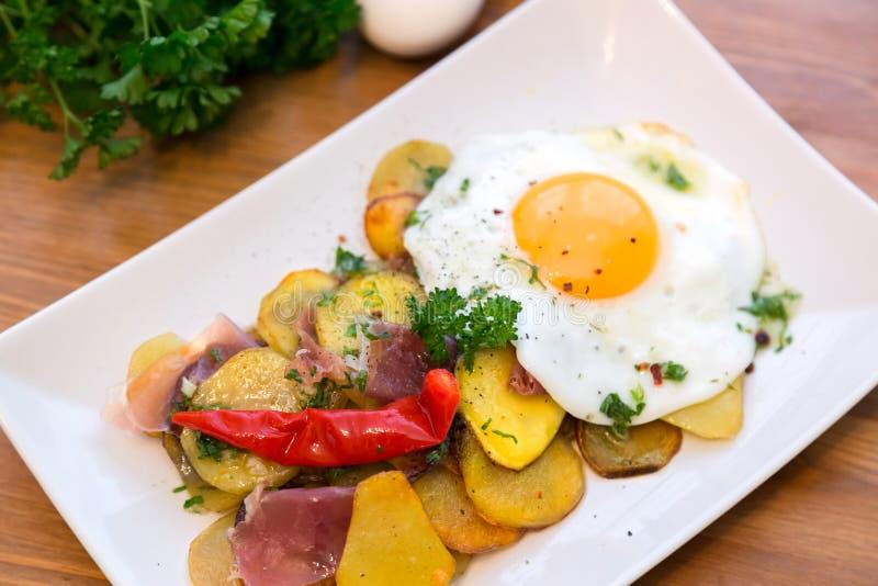 Patata y huevo asados, rotos de Huevos imagen de archivo