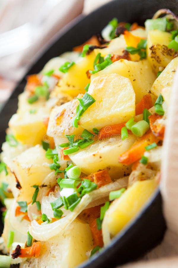 Patata, zanahoria y cebolla en un sartén grande foto de archivo