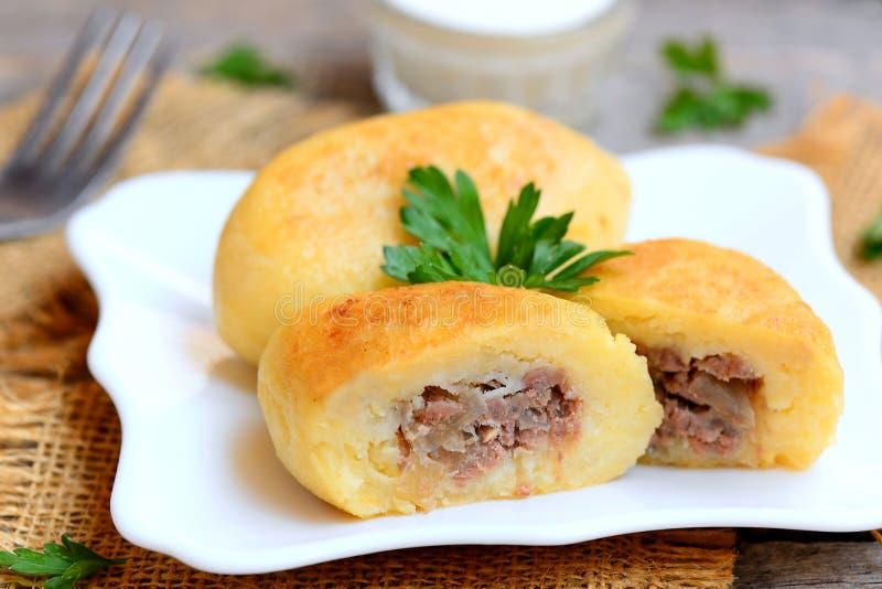 Patata zrazy con una carne che riempie su un piatto bianco e su una tavola di legno d'annata Ricetta zrazy ucraina tradizionale c immagini stock