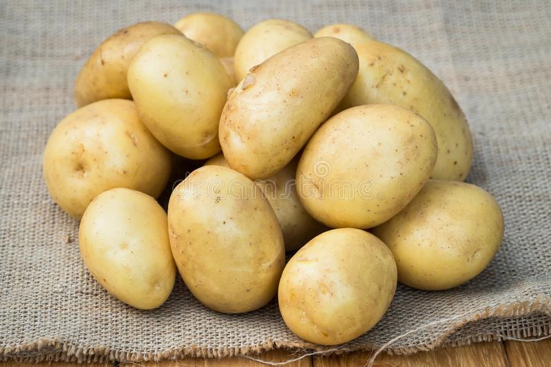 Patatas amarillas jovenes en harpillera fotografía de archivo libre de regalías