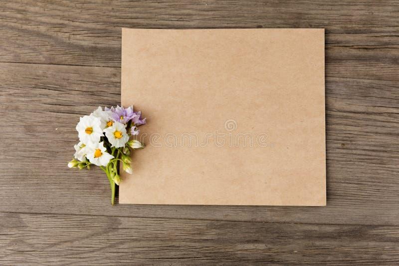 Patatas blancas y flores púrpuras con el documento en blanco del arte sobre fondo de madera del viejo grunge Visión superior Maqu fotos de archivo