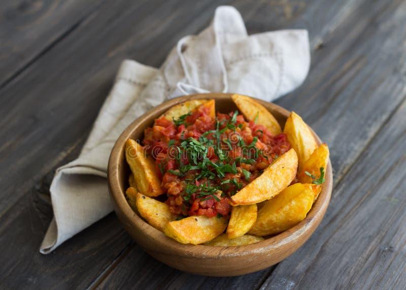 Patatas Bravas,被烘烤的土豆用辣西红柿酱 库存照片