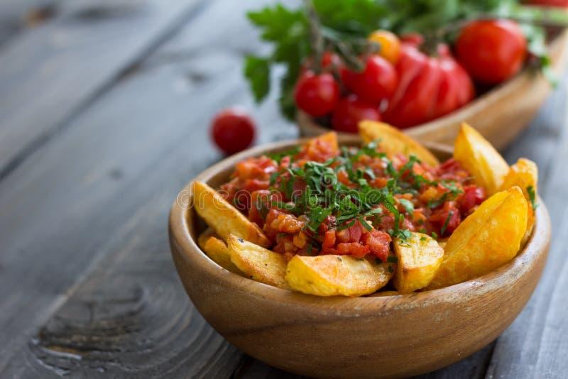 Patatas Bravas, baked potatoes with spicy tomato sauce. Patatas Bravas, traditional Spanish tapas, baked potatoes with spicy tomato sauce in wooden bowl on royalty free stock photography