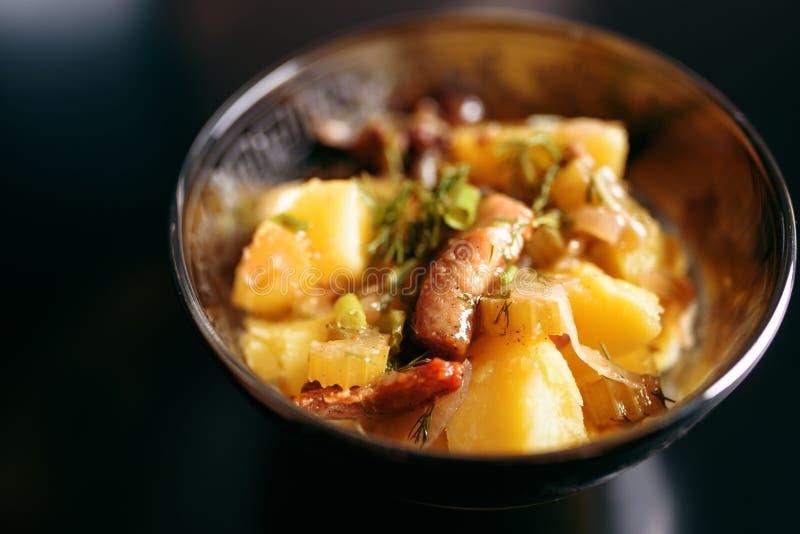 Patatas cocidas con la carne en una placa en un fondo negro fotografía de archivo
