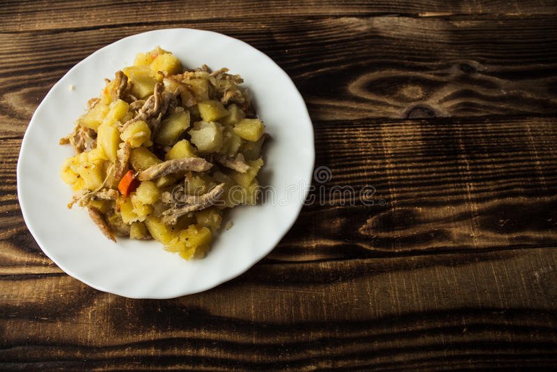 Patatas cocidas con la carne, las zanahorias y las cebollas imagenes de archivo